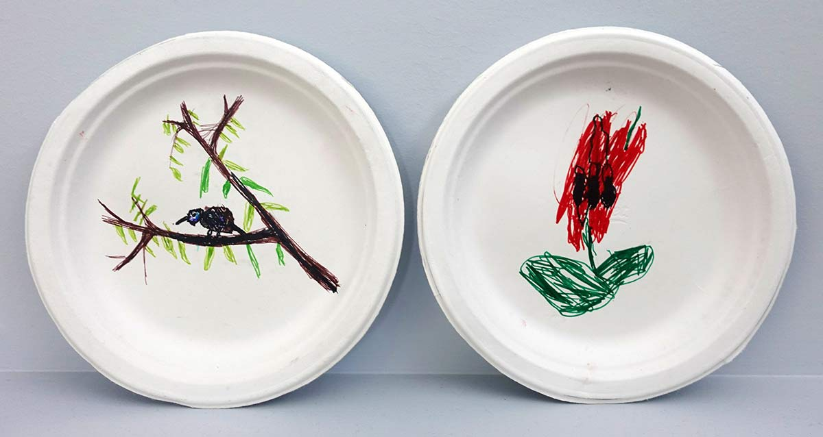 Two plates, with rough drawings of a bird on a branch on one, and a red flower on the other. - click to view larger image
