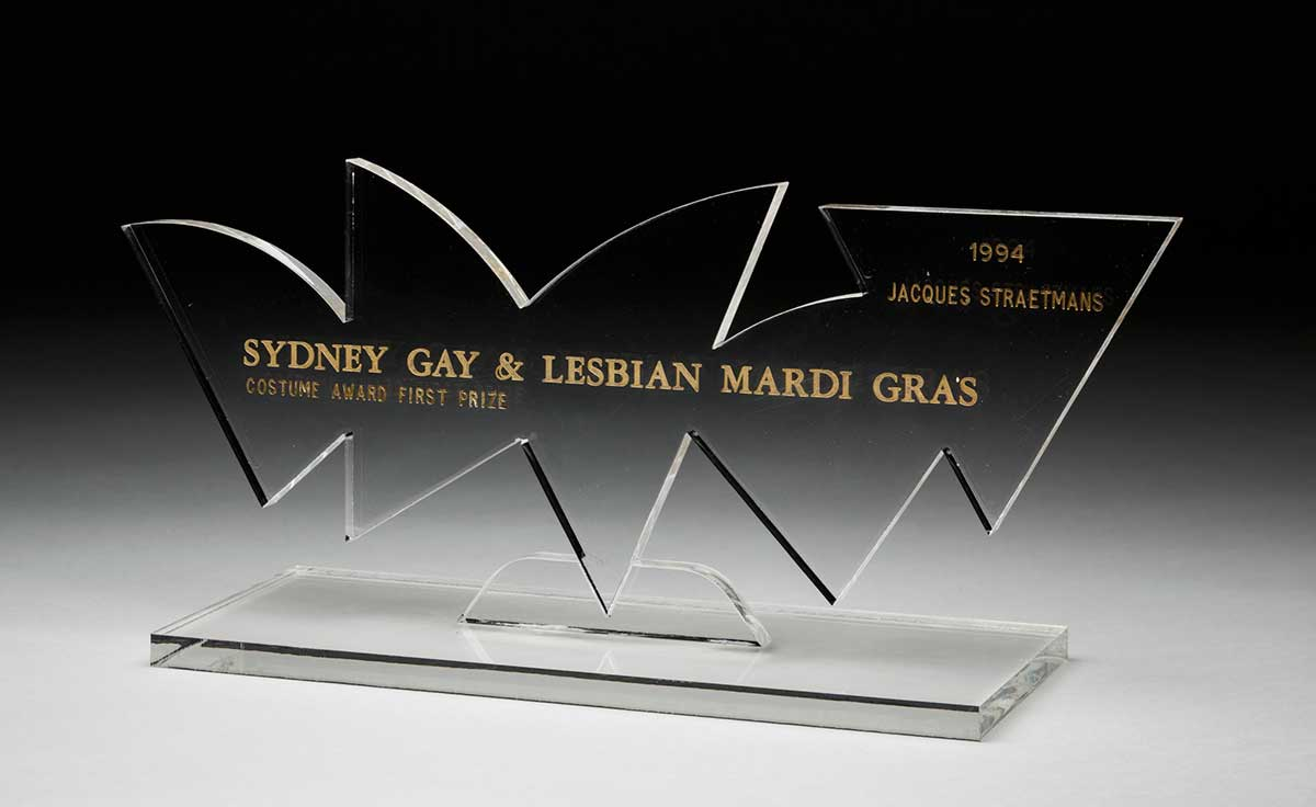 Trophy in the form of an irregularly-shaped vertical clear acrylic panel [reminiscent of the Opera House sails] on a rectangular clear acrylic base.