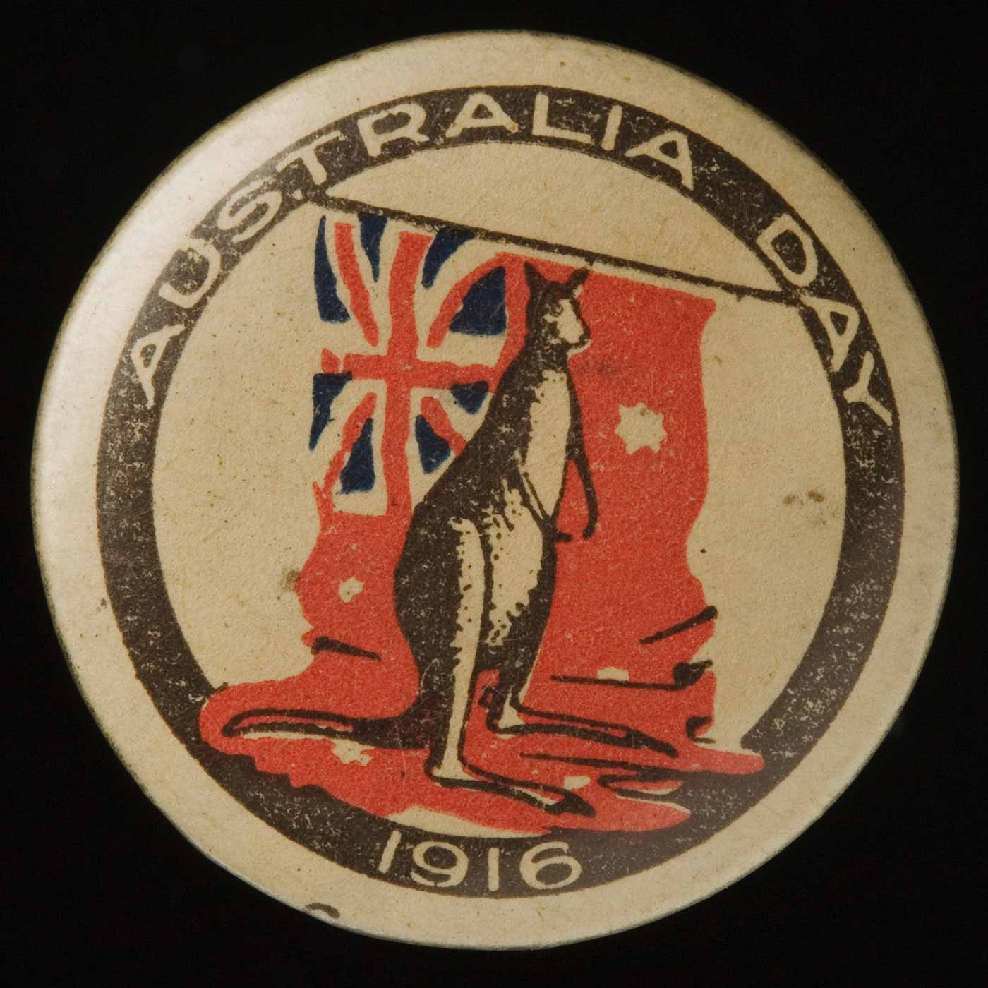Circular badge with 'Australia Day 1916' printed in a black circular band. The central image shows a kangaroo standing on a red ensign. - click to view larger image