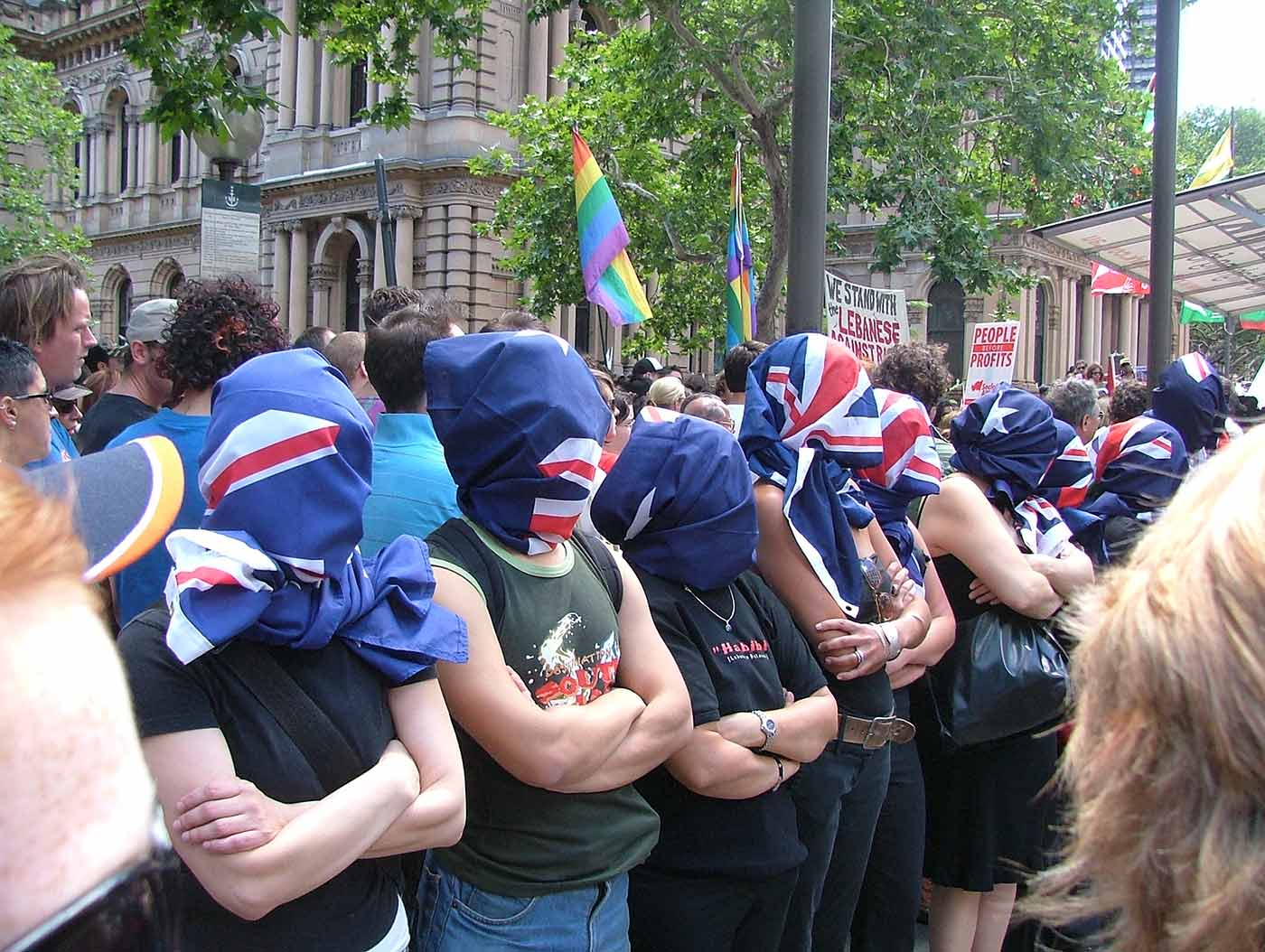 Nine people stand with arms crossed and their heads wrapped in Australian flags. - click to view larger image