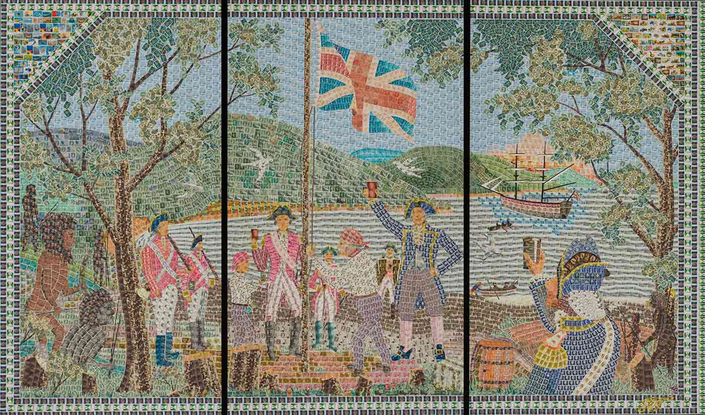 A mural in three panels, made up of hundreds of postage stamps, depicting a flag-raising ceremony by English military men. Aboriginal men stand watching, to the left of the mural. Two of the soldiers hold raised glasses to the Union Jack. A sailing ship is moored off the coast and green hills appear in the background. - click to view larger image