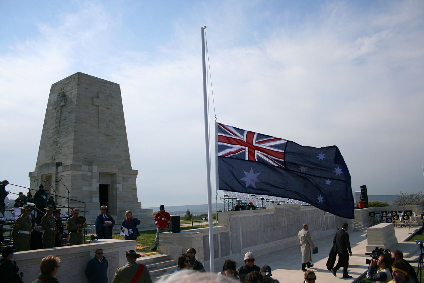 A colour photograph of a ceremony at the Lone Pine Memorial at Gallipoli. The Memorial is in the background and an Australian flag at half mast flies in the foreground. - click to view larger image