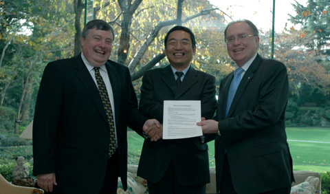 Craddock Morton (on right) stands hand-in-hand with Tetsuo Taniya (centre) and and Murray McLean (on left), who holds the memorandum of understanding.