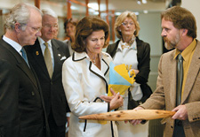 Curator David Kaus explaining the workings of a shield to His Majesty King Carl XVI Gustaf and Her Majesty Queen Silvia of Sweden.