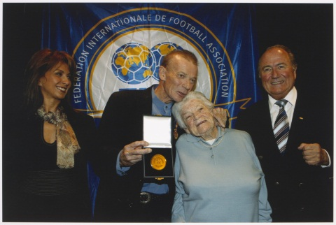 Colour photograph showing four people standing in front of a blue gold and white banner with the words 'FEDERATION INTERNATIONALE DE FOOTBALL ASSOCIATION' printed around a logo of two soccer balls superimposed on globes. A man at the centre has his arm arond a woman and his chin rests on the top of her head. The man holds a gold medal in a presentation case in his right hand. A woman stands to his left and a man to his right.