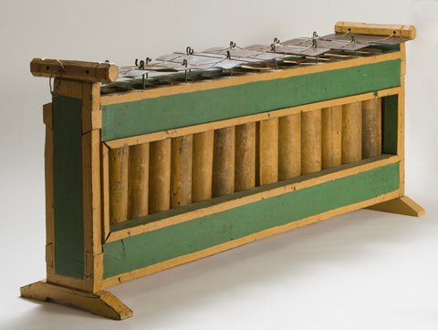 A wooden instrument featuring fourteen metal cylinders, painted yellow and encased in a rectangular wooden frame. There are fourteen rectangular metal slats on the top, of varying sizes and strung together with string, which is suspended from metal hooks. The wooden case is painted yellow and green.