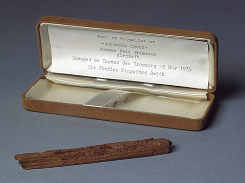 Wooden fragment with 'Southern Cross 12.5.35' printed on one side. The fragment is stored in a Parker Pen box covered in yellow fabric, with a typed note attached to the inside lid.
