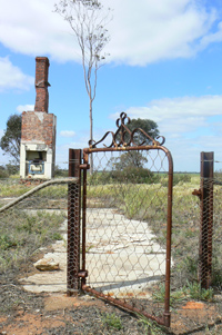 Rusted metal gate at the front of old house foundations. A brick chimney appears at the rear of the image.