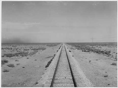 Black and white photograph of a straight section of railway line, surrounded by desert.
