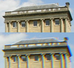 A view looking up at the upper part of a large sandstone building. The view is seen twice, one upon the other. The building has large classical-style half-columns, five windows and a slate-covered roof surrounded by a balustrade-type structure. Behind the building can be seen sky and clouds. In the upper view of the building, the image is sharp and clear. In the lower view, the image is slightly blurred and a purple tinge can be seen along the right-hand edges of the building.