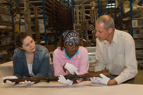 Theresa Ross with two Museum staff members examining a rifle.