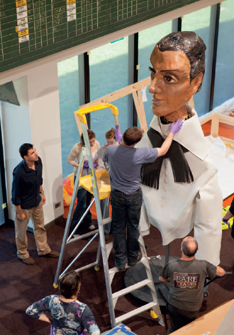 Photograph taken from above, looking down at an oversized puppet consisting of a female face, constructed of painted papier-mache. The woman wears a white collared-shirt and black taselled scarf. A man on the third rung of a large ladder reaches up to adjust the puppet's collar. Five other people stand in the gallery space.
