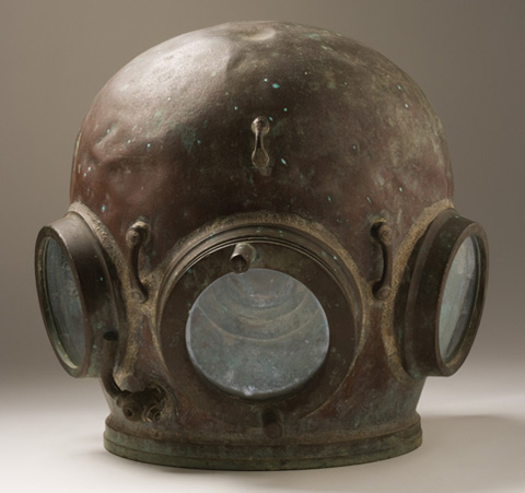A rounded brass diving helmet with three circular glass windows.