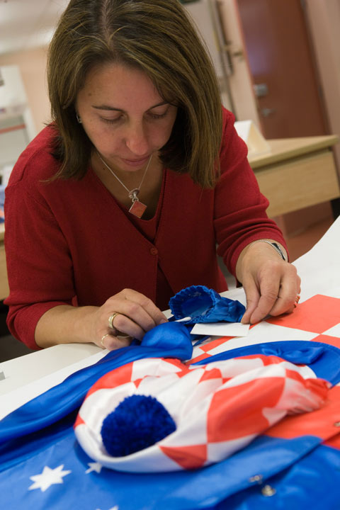 Conservator Carmela Mollica removes the adhesive residue from the double-sided tape used to adhere the jockey silks to a backing board before placing them into a frame.