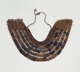Horseshoe-shaped, collar-like breast ornament or gorget made of cane, coconut fibre, dog hair, shark teeth and feathers.