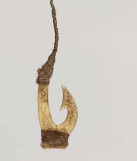 Fishhook made of two pieces of bone bound together with a string made from plant materials. The barb located on inner side of hook with a brown fishing line attached.