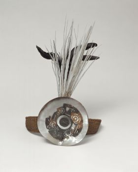 Headband made of coconut fibres, interwoven, and attached to a round plate of Mother-of-pearl where long black and white tail feathers protrude behind it.