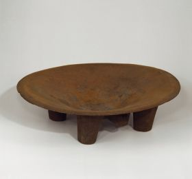 Kava bowl made of one piece of wood that is round and shallow, and rests on four legs.
