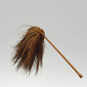A fly-flap or whisk, made of coconut fibres, affixed to a wooden handle of reddish–brown colour, polished and bulged at both ends and a tassel of blackish-brown coconut fibres.