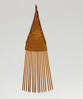 A comb made of sixteen small sticks held together by a weave of light brown fibres.