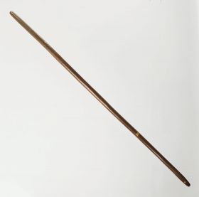 Digging stick made of a dark brown heavy wood.