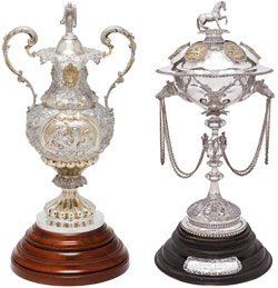 The Melbourne Cup trophy is mostly silver with two ornate handles and mounted on a wooden base. The Queen's Plate trophy has a horse on the top standing a rounded silver globe mounted on a long stem. Chains are draped from the globe.
