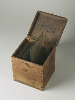 A wooden box, shown with the lid open, and three glass plates inside, held in place by vertical wooden slats.