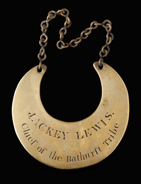 A gold crescent-shaped gorget imprinted with the words 'JACKEY LEWIS, Chief of the Bathurst Tribe'.