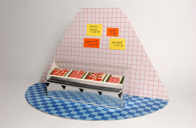 A diorama of the interior of a Butcher's shop, consisting of a blue checkered patterned semi circle cardboard base, a pink and white checkered triangular carboard background and a cardboard and plastic display case filled with modelling compound 'steaks' and 'sausages'.