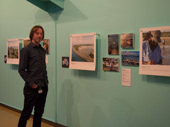 A man stands next to a gallery wall featuring a number of large photographs.