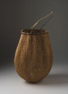 Colour photograph of a basket with handle at top and conical-shaped base.