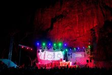 A stage with lights, set in a rocky landscape.