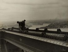 Two workers adjust the track for a 'creeper' crane atop a metal section of bridge.