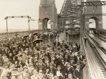 Black and white photo of a large crowd of schoolchildren crossing the Sydney Harbour Bridge. There is no traffic on the bridge.
