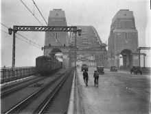 A black and white photograph of cars, two cyclists and several cars crossing the Sydney Harbour Bridge.