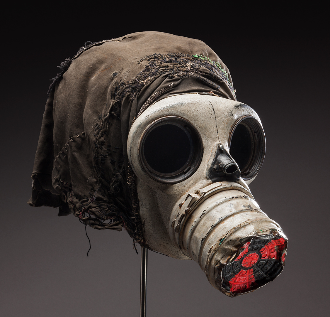 Gas mask with black cloth attached to the back and the international symbol for radiation painted in red on the nose cone