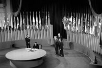 black and white photo of five suited men standing in a large room