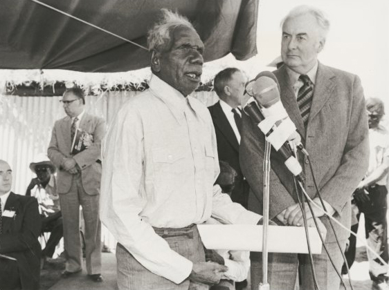 Aboriginal man holding document speaks in front of microphones on stand, with Prime Minister Whitlam to his left.