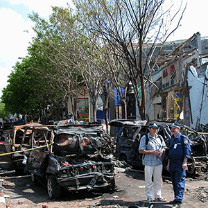 two AFP officers confer in the street. Behind them are the burnt-out remains of vehicles and a wrecked building