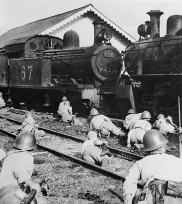 Soldiers crawling towards a steam engine.