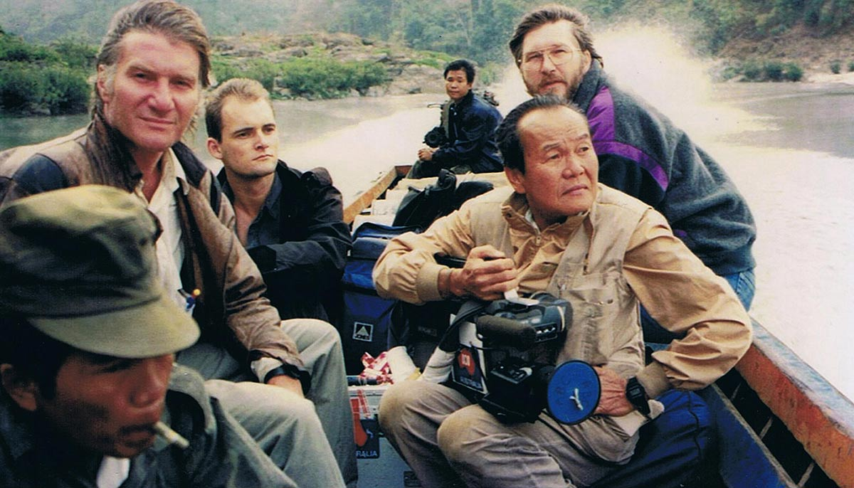 A group of men in a boat. One is holding a camera.