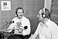 two men sitting in a radio studio in front of microphones. They are smiling and clearly in conversation. The present is wearing a top saying �We�re talking your language on 3EA�