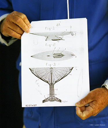 a close-up photo of two hands holding onto the design of a yacht keel