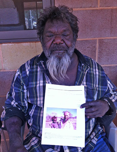 An Aboriginal man sits holding a printed image of himself as a young boy, with a man.