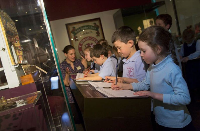 Group of school children writing notes in front of a museum display case.