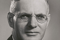 cropped studio black and white photo of Curtin.  He is wearing a dark suit and glasses
