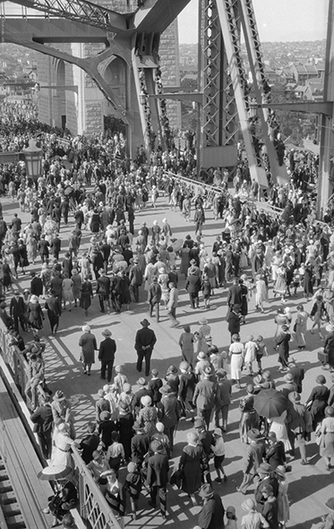 High shot showing hundreds of people crossing the road deck.