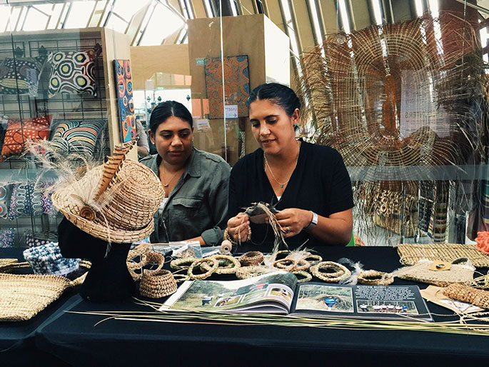 Two women sitting at a table with various woven objects
