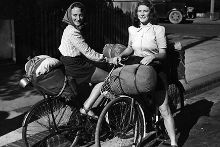 Black and white photo of two women on bicycles carrying swags and other equipment