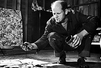 Black and white photo of balding, middle-aged man crouches by canvas spread on the floor. He has a cigarette in his mouth, a paint can in one hand. His other hand seems to be covered in paint. He is frowning intently at the canvas, which has a few splotches of dark paint on it.